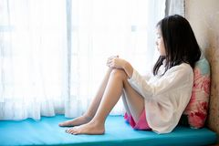 Asian girl waiting,sitting and looking at the window in home stock image