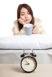 Asian girl  wake up  with alarm clock and  coffee cup Royalty Free Stock Image