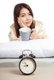 Asian girl  wake up  with alarm clock and  coffee cup Stock Photography