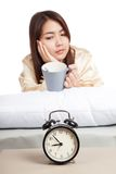 Asian girl  wake up  with alarm clock and  coffee cup Stock Photo