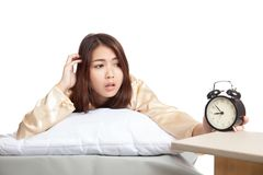 Asian girl  wake up late  look at alarm clock Royalty Free Stock Photo