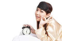 Asian girl wake up show OK with eye mask  and alarm clock Royalty Free Stock Photos