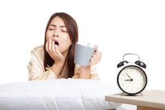 Asian girl wake up , yawn with alarm clock and coffee cup. Isolated on white background royalty free stock photo