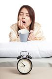 Asian girl wake up , yawn with alarm clock and coffee cup. Isolated on white background stock images