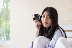 Asian girl  waking up late. Asian girl looking alarm clock after waking up late Stock Images