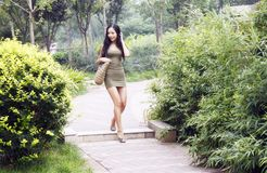 Asian girl walking in park. Beautiful Asian girl walking in a park Royalty Free Stock Images