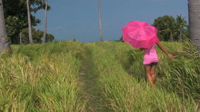 Filipino woman walking along a green grass field in the Philippines stock footage