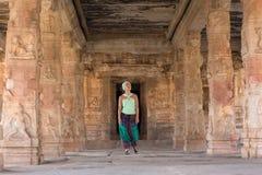 Asian girl walks among the pillars of an ancient temple. A beautiful girl walks among the columns of an ancient temple and looks at them with interest Royalty Free Stock Photos