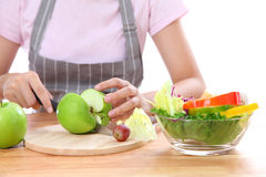 Asian girl was carrying a knife, cut the apple to salad vegetabl Stock Photos
