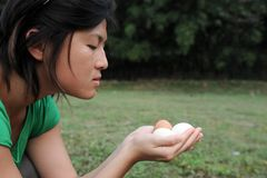 Asian girl watches eggs Stock Images
