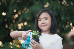 Asian girl watering a red flower in the garden Royalty Free Stock Image