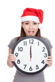 Asian girl wear red christmas hat excited with clock at midnight Stock Photos