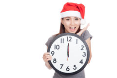 Asian girl wear red christmas hat excited with clock at midnight Stock Images