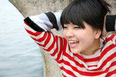 Asian girl wearing colorful stripes smiling. Colored stripes worn by a young Asian girl smiling Royalty Free Stock Image