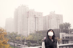 Girl in air pollution. Asian girl wearing mouth mask against haze air pollution in beijing Royalty Free Stock Image