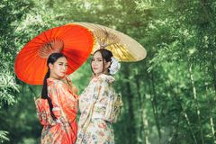 Asian girl wears a kimono and holds a traditional Japanese umbrella. stock images