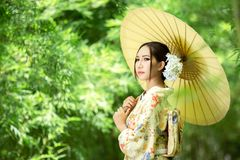 Asian girl wears a kimono and holds a traditional Japanese umbrella. royalty free stock images