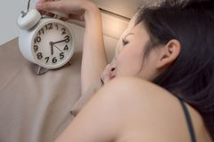 Asian girl on white bed wake up late look at alarm clock. In morning Royalty Free Stock Photos