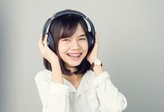 Asian girl in white casual dress listening to music from black headphones. stock images
