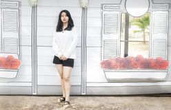 An Asian girl in white cloth and black shorts standing on the wh. Ite wall Royalty Free Stock Image