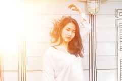 An Asian girl in white cloth and black shorts standing on the white wall. With sun flare effect Royalty Free Stock Photo