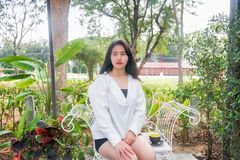An Asian girl in white coat sits and places a black cup of coffee in her hand on the white bench under the morning light. An Asian girl in white coat sits and Royalty Free Stock Images