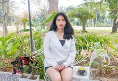 An Asian girl in white coat sits and places a black cup of coffee in her hands on the white bench under the morning light. An Asian girl in white shirt sits and Royalty Free Stock Photo