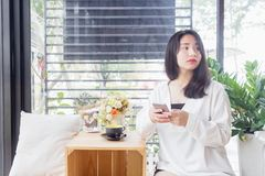 An Asian girl in white coat sitting and playing mobile phone in the glass room of vintage cafe in Bangkok, Thailand January 3,2017. An Asian girl in white coat Stock Images