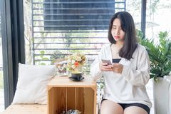 An Asian girl in white coat sitting and playing mobile phone in the glass room of vintage cafe in Bangkok, Thailand January 3,2017. An Asian girl in white coat Stock Photos