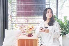 An Asian girl in white coat sitting and playing mobile phone in the glass room of vintage cafe in Bangkok, Thailand January 3,2017. An Asian girl in white coat Stock Photography