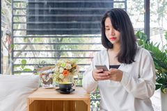 An Asian girl in white coat sitting and playing mobile phone in the glass room of vintage cafe in Bangkok, Thailand January 3,2017. An Asian girl in white coat Royalty Free Stock Photography
