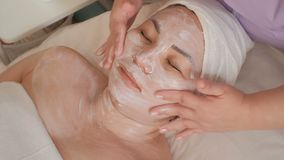 Asian girl with white cream on the face with closed eyes in the beauty salon . Massage in the beauty salon. The process of rejuven. Asian girl with white cream stock video