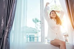 Asian girl who just wake up in the morning. As relaxed and smiling. She opened the window to receive the light of the morning sun stock photos