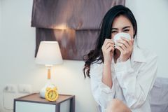 Asian girl who just wake up in the morning. As relaxed. She opened the window to receive the light of the morning sun. She was holding a cup of coffee or tea to royalty free stock photo