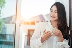 Asian girl who just wake up in the morning. As relaxed. She opened the window to receive the light of the morning sun. She was holding a cup of coffee or tea to Royalty Free Stock Images