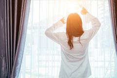 Asian girl who just wake up in the morning. As relaxed and smiling. She opened the window to receive the light of the morning sun royalty free stock images