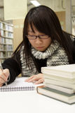 An Asian girl who is reading and studying. She is staying in library of a University for the upcoming mid-term exams. She is very concentrated and working very Stock Image