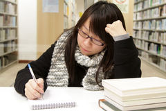 An Asian girl who is reading and studying. She is staying in library of a University for the upcoming mid-term exams. She is very concentrated and working very Stock Images