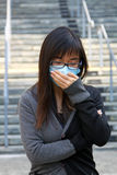 Asian girl who is sick and wearing mask. It was taken on campus in a Unversity, a sick girl probably because of exam Stock Image