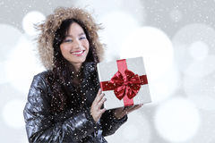 Asian girl with winter jacket holds gift box. Picture of happy asian teenage girl wearing winter jacket and smiling at the camera while holding a gift box with Royalty Free Stock Photo