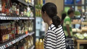 Asian girl, woman walking, looking and shopping for sauce in supermarket isle