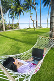 Asian girl work in hammock with laptop at beach Royalty Free Stock Image
