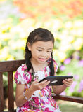 Asian Girl write an note pad. In the flower park for play a tablet game Royalty Free Stock Images