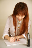 Asian girl writing notes Stock Images