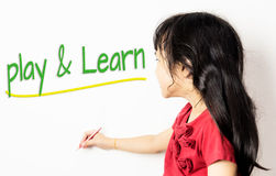 Asian girl wrote play and learn on white. Royalty Free Stock Images