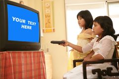 Asian girls as princess, tv remote control royalty free stock photography