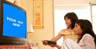 Asian girls as princess, tv remote control. Two asian girls dressed as princess, tv remote control, blue copy space Royalty Free Stock Image