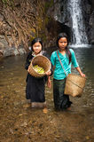 Asian girls with baskets at rain forest near tropical waterfall. VANG VIENG, LAOS - 15 DEC, 2013: Unidentified cute Asian girls with baskets washing vegetables Stock Photos