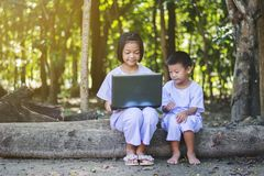 Asian girls and boy using notebook of searching some information. At countryside of Thailand royalty free stock images
