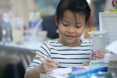 Asian girls are coloring happily in school stock image